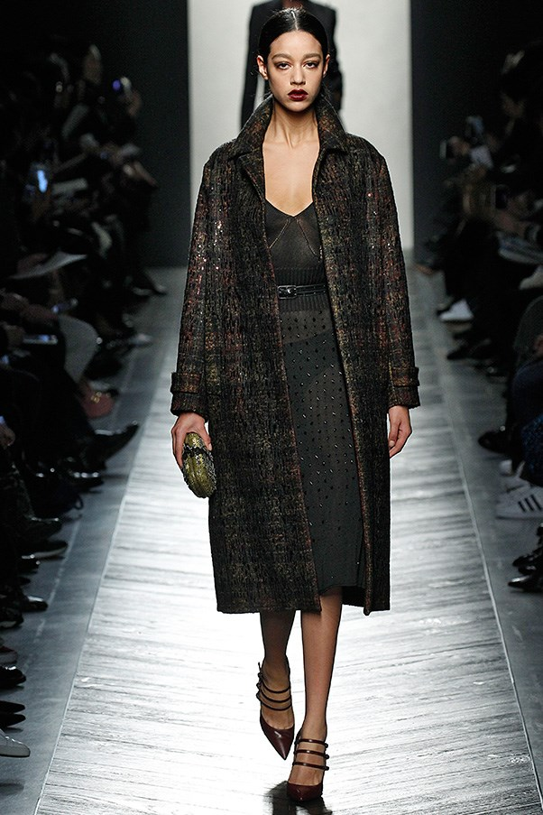 "<strong>BOTTEGA VENETA</strong> <BR><BR> Evening carried through the idea of subtlety with the same cinched silhouette rendered in a slightly sheer dress sprinkled with micro sequins and built-in tonal bras. It was all covered up though, by a sequined plaid coat. Again, Maier was firmly grounded this season and wanted his customer to have something she could look at and say, ""I could realistically wear that."""
