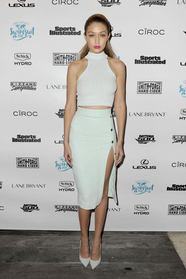 Looking fresh and youthful in an all white outfit, Hadid teams a turtleneck crop top with a pencil skirt and matching ivory pumps.