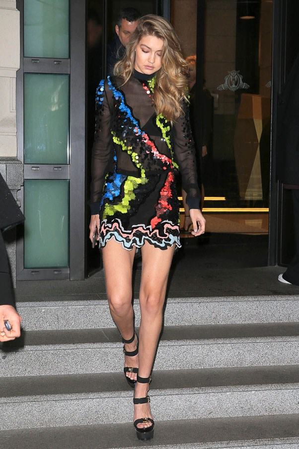 The model appropriately dressed for a night out in a colourful Versace mini dress and platform heels.
