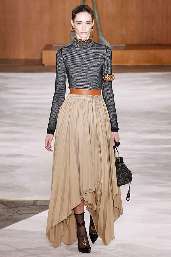 <strong>LOEWE</strong><BR><BR> There was an air of grownup dressing to this season in the lineup of snug tops and pleated or flowing full skirts—all cut with hanky hems. If this was his canvas, from there, he added in carefully placed jewelry and accessories. Golden discs turned into earrings, chain chokers, arm bands and even details on strappy sandals.