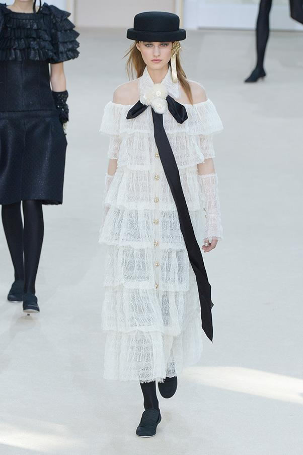 <strong>CHANEL</strong><BR><BR> The final looks were a parade of gauzy black and white mini dresses and gowns, with pearl buttons or leather stitching. A tiered white lace dress was intrinsically Chanel—it preceded the final dress which features double C logos. Lest you forget who's boss. — <em>Kerry Pieri</em>