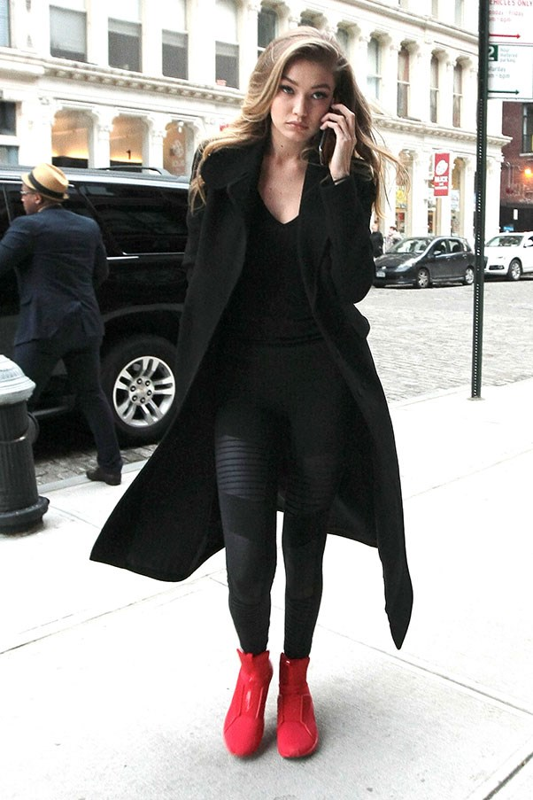 Gigi spiced up her all black ensemble with bold red (and <em>very </em>hard to get) FENTY x Puma kicks.