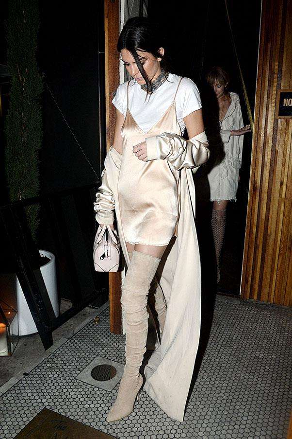 The model gave us a new take on the classic slip dress with this shorter version, which she styled over a white tee and paired with taupe thigh-high boots.