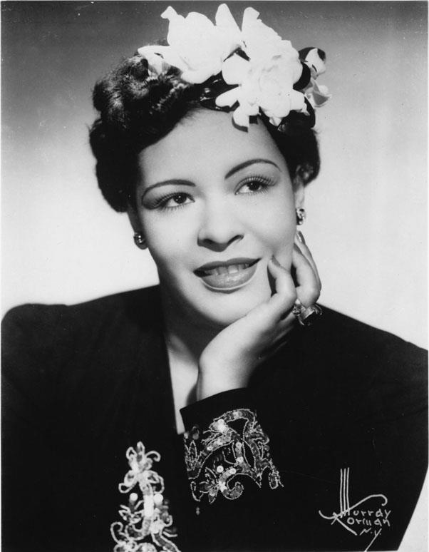 <strong>1938: UPDO WITH FLOWERS</strong> <br><br> Though she was known primarily for her iconic voice, Billie Holiday's stardom also popularized elegantly accenting hairstyles with flowers — specifically white gardenias.