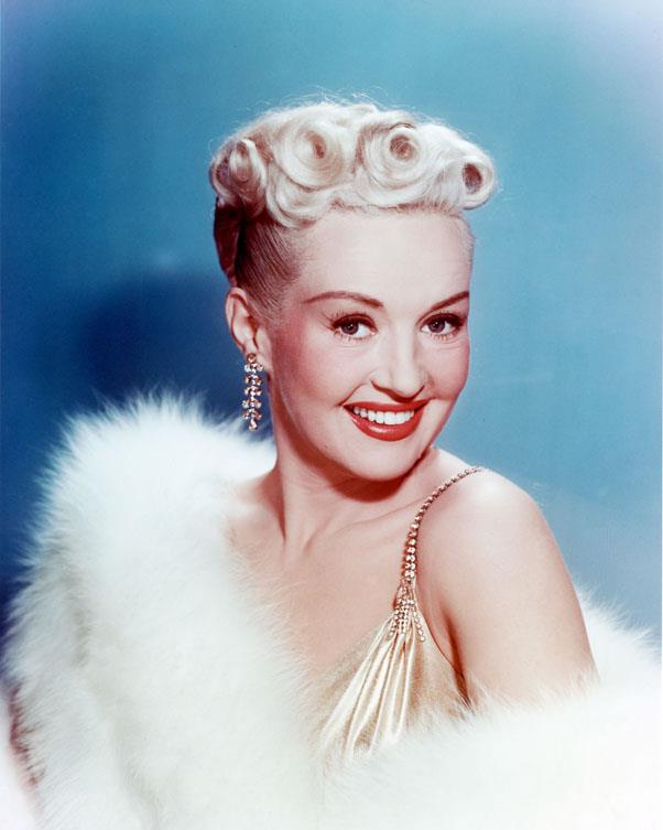<strong>1942: GLAM PIN CURLS</strong> <br><br> Not content to keep things basic, stars like Betty Grable brought pin curls and finger waves to the next level with bold blonde hair, red lipstick, and fun fashion.