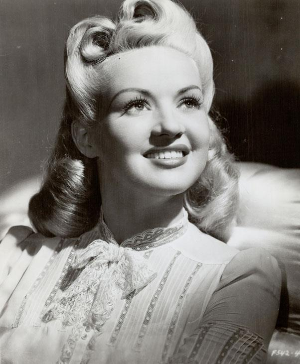 """<strong>1945: VICTORY ROLLS</strong> <br><br> After the war, many women signaled their celebratory feelings with a voluminous style dubbed """"victory curls"""" — a 'do that would become one of the era's most famous."""