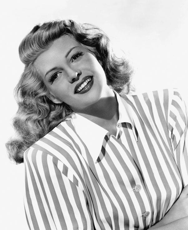 <strong>1946: LOOSE CURLS</strong> <br><br> A softer curled style stayed popular throughout the era, with stars like Rita Hayworth maintaining a deep side part and full waves.
