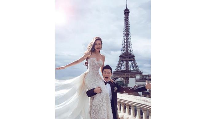 """<strong>Angela Yeug and Huang Xiaoming</strong> <br><br> <strong>The dress: </strong>The bride wore Elie Saab in a pre-wedding photoshoot in paris, and a custom Dior gown for the wedding. <br><br> <strong>The cake:</strong> The cake was approximately 30 metres tall, and shaped like a carousel. <br><br> <a href=""""https://www.instagram.com/p/8lE3sDnYX4/"""">@eliesaabworld</a>"""