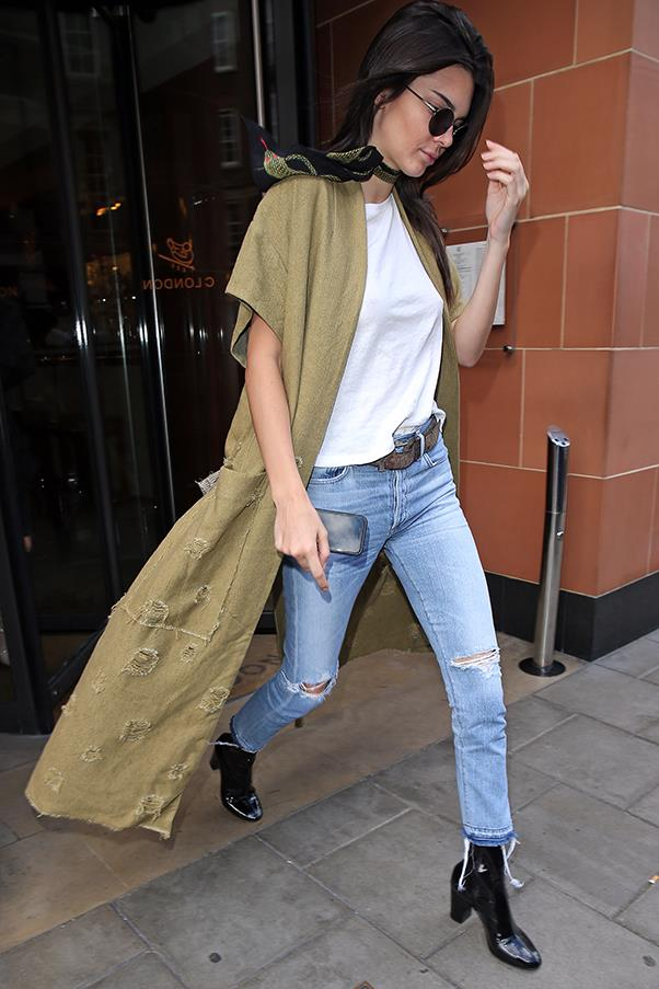 <strong>May 23, 2016</strong> <br><br> Kendall stepped out in London ready for the chill weather in a distressed jeans and white tee combo, finished with a trench vest, scarf and leather boots.