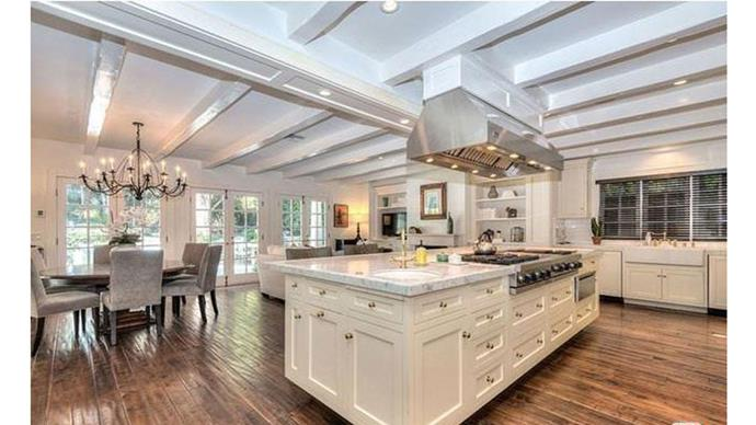 The stylish kitchen-cum-dining room, fit with marble counter-tops and wooden floors.