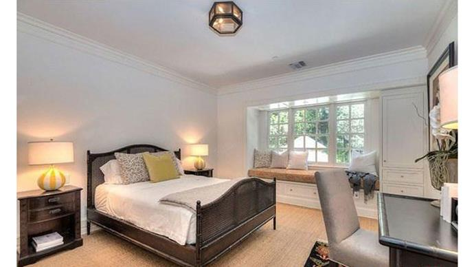 A guest bedroom featuring stylish, dark-wood furniture.