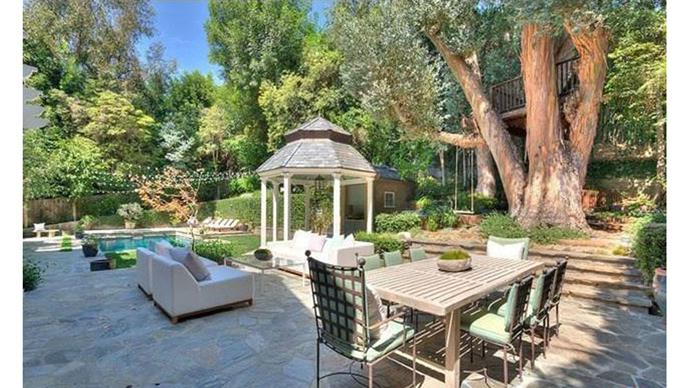 The large backyard; fit with hanging tea-lights, a pool and a gazebo.