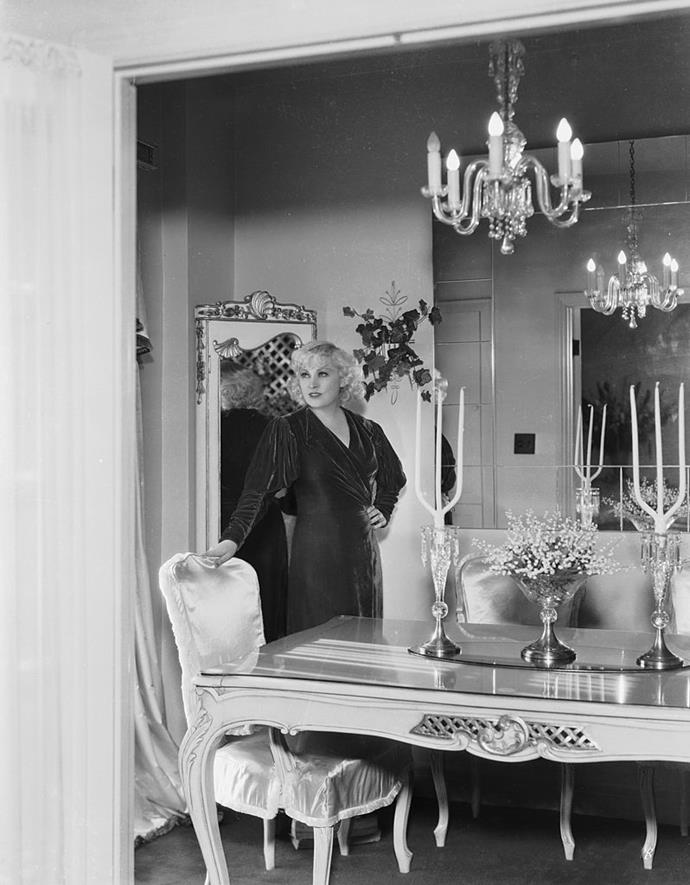 <strong>1935</strong> <br><br> Actress Mae West ushers in a more romantic look, with glimmering glass chandeliers, a detailed table, and a shapely seat.