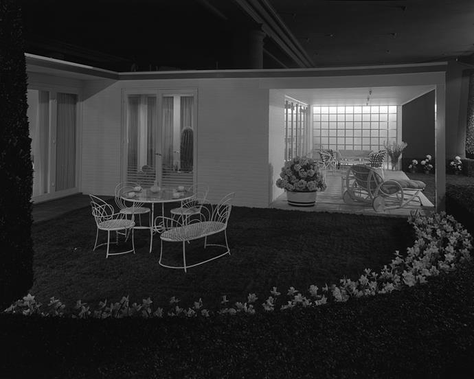 "<strong>1937</strong> <br><br> Another ""Modern House,"" this time, seen from the outside. Curvy details on the patio set have a slightly more feminine feel, while the window mimics the so-trendy look of glass block tiles."