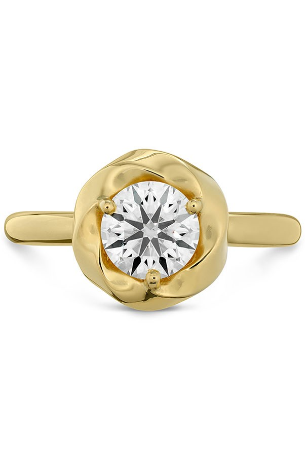 """<strong>Simple and Elegant</strong> <br><br> <strong>Your ring has:</strong> A bezel setting <br><br> <strong>You are:</strong> No fuss, no muss. """"You're the ultimate minimalist,"""" Sabatino says. """"You want something that lasts through all the trends and fads."""" You appreciate fine craftsmanship and covet a ring that will last a lifetime. <br><br> <em>Hearts on Fire Atlantico Wave Halo Solitaire Engagement Ring</em>, <a href=""""http://www.heartsonfire.com/shop-jewelry/rings/engagement-rings/atlantico-wave-halo-solitaire-engagement-ring.aspx#GUyrYXt6PycqRXjv.97"""">heartsonfire.com</a>"""