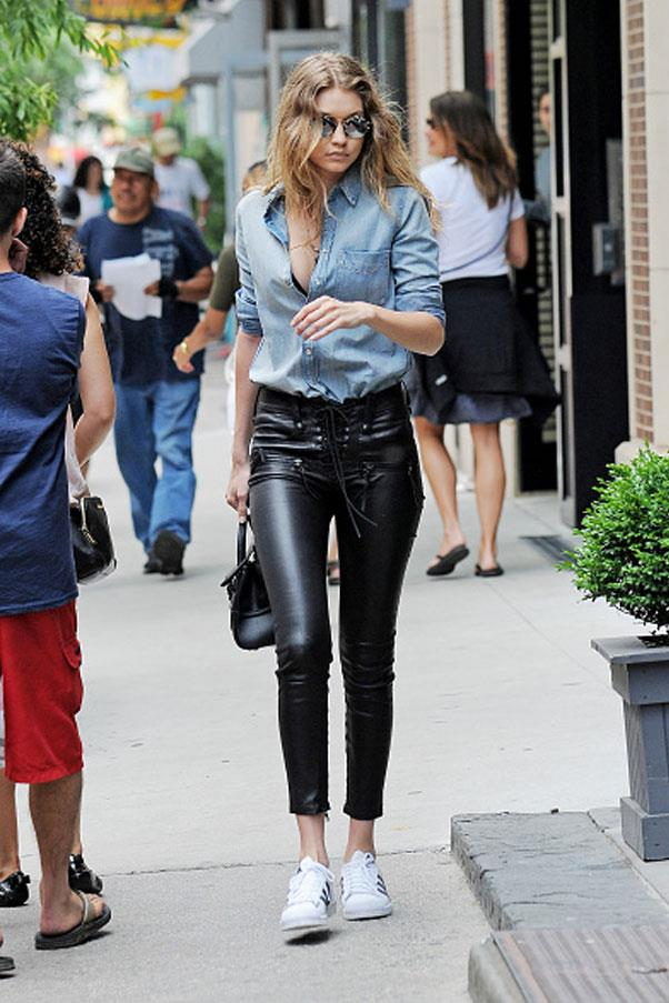 Gigi stepped out in New York city in a cool ensemble, complete with a denim button-down shirt, leather pants by Unravel and Adidas superstars.