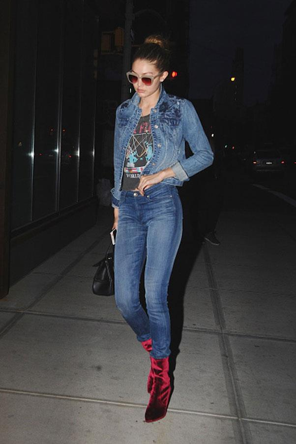 Gigi opts for a daring head-to-toe denim combination, complete with contrasting red velvet boots.
