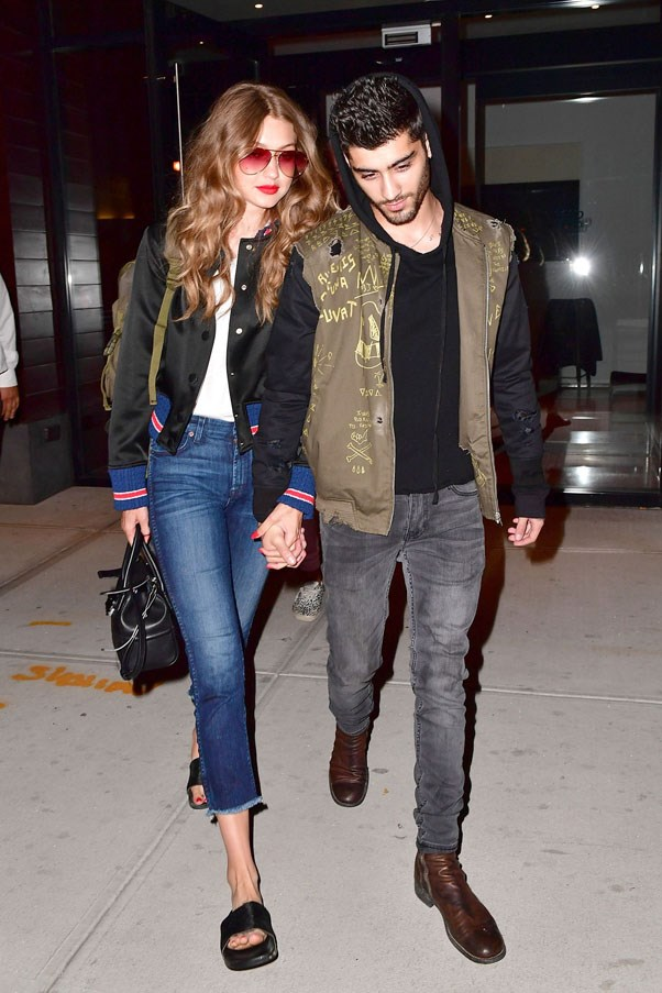 Matching boyfriend Zayn Malik's bomber jacket style, Gigi paired the look with white tee, 7 for All Mankind high-waisted raw hem cropped jeans, black slides and tinted aviator sunglasses.