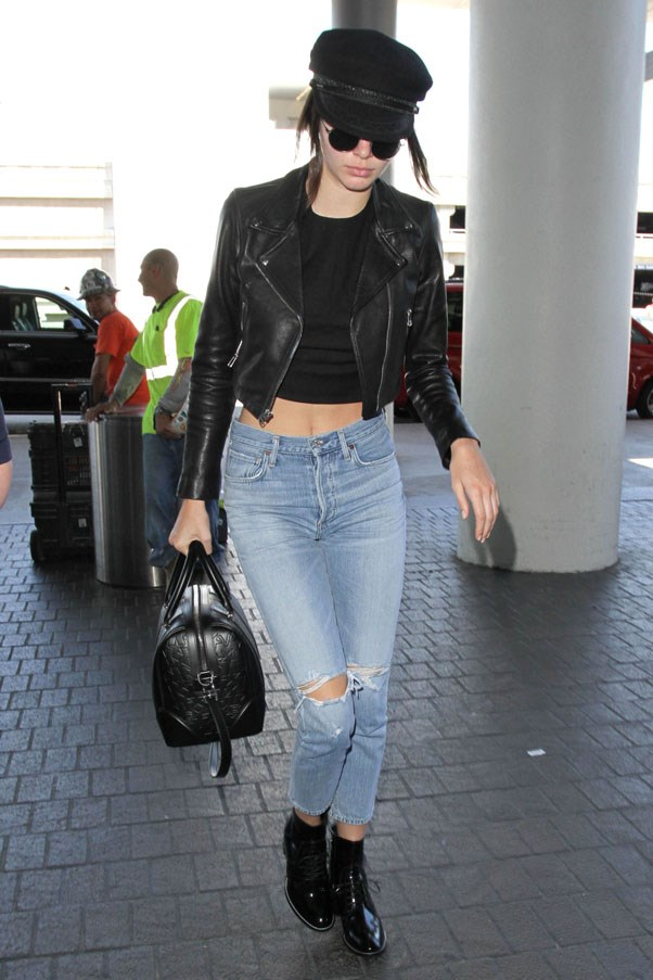<strong>July 5, 2016</strong> <br><br> Kendall kept it laid back and cool at the airport, wearing a black crop top, motorcycle jacket, newsboy cap and distressed denim by Citizens of Humanity.