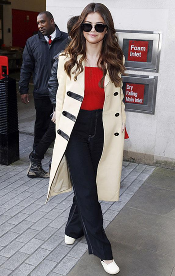 <strong>March 11, 2016</strong> <br><br> Gomez opted for a polished look, wearing high-waisted denim, red bodysuit, cream trench and white pumps.