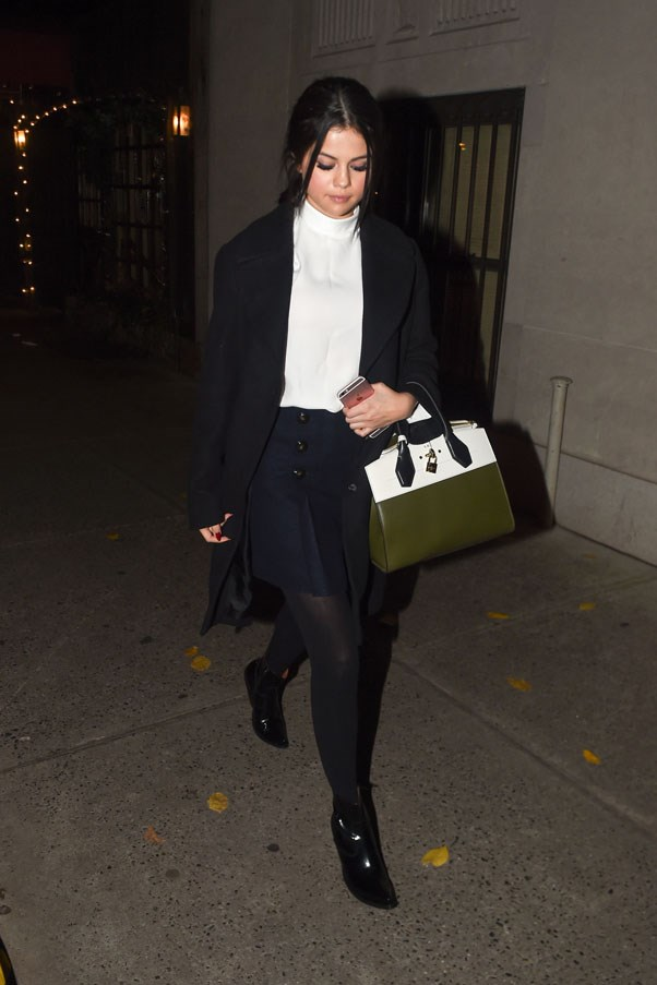 <strong>December 10, 2015</strong> <br><br> Wearing a pleated navy skirt, white turtleneck, black coat and olive green bag, Selena was spotted leaving Lady Gaga's parent's restaurant in New York.