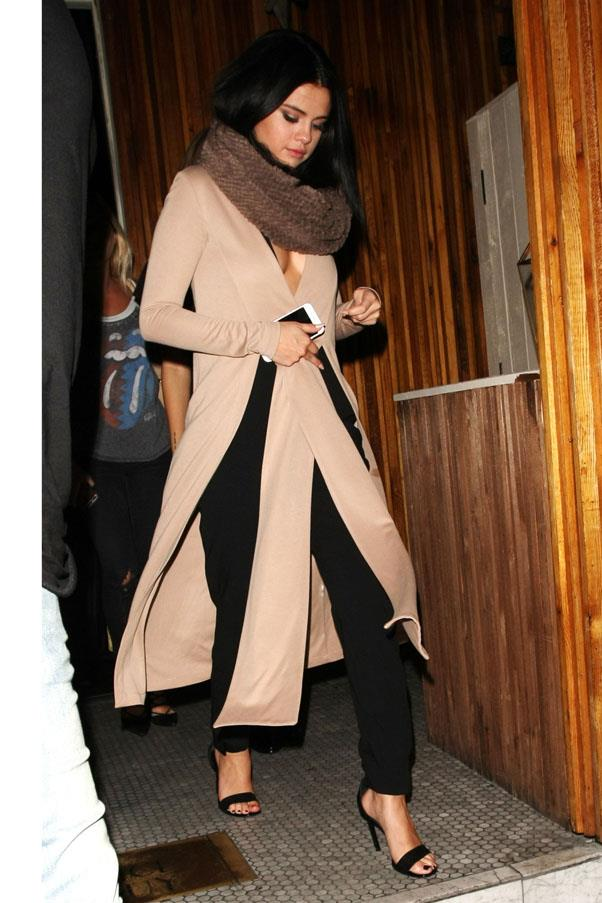 <strong>November 1, 2015</strong> <br><br> Selena stepped out in a plunging camel sweater, fur scarf and black trousers.