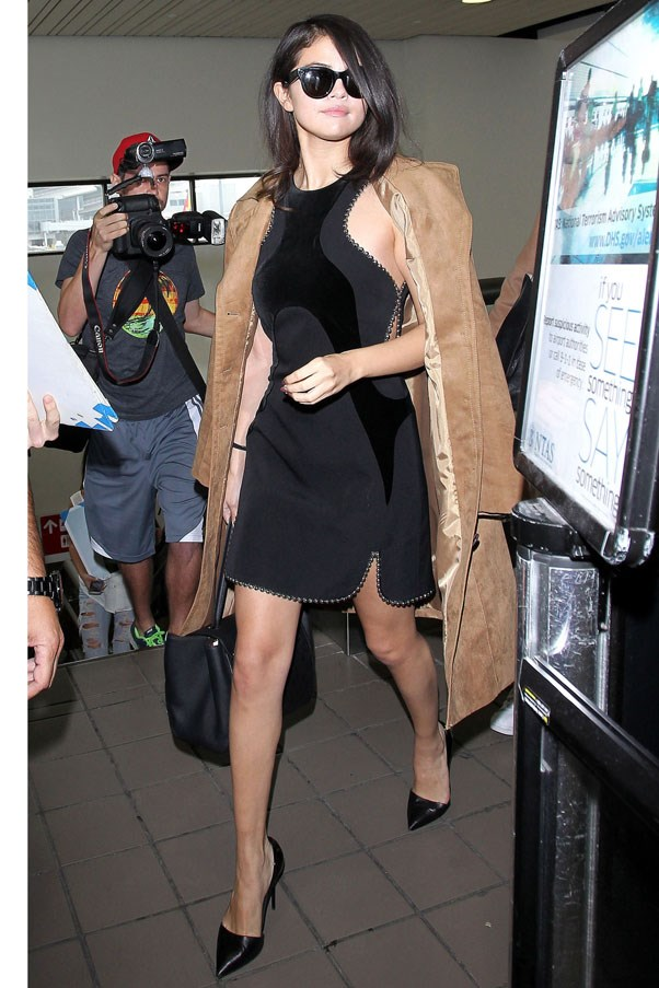 <strong>October 16, 2015</strong> <br><br> Selena upped her airport style game wearing a chain-trimmed Alexander Wang dress and H&M coat with Giuseppe Zanotti pointy-toe pumps at LAX.