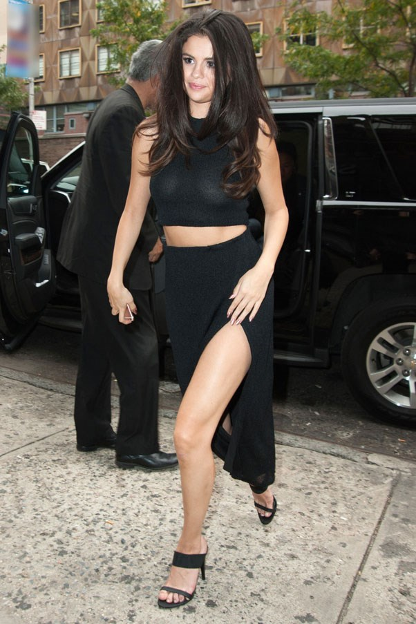 <strong>October 13, 2015</strong> <br><br> Selena pairs the it-girl's go-to black crop top with a thigh-high split skirt by Markoo Studios and Jenni Kayne mules.