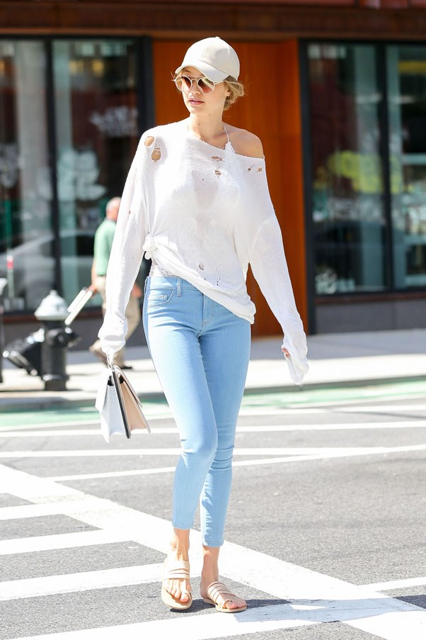 Gigi pairs distressed jeans with a white knit, cap, and flat sandals.
