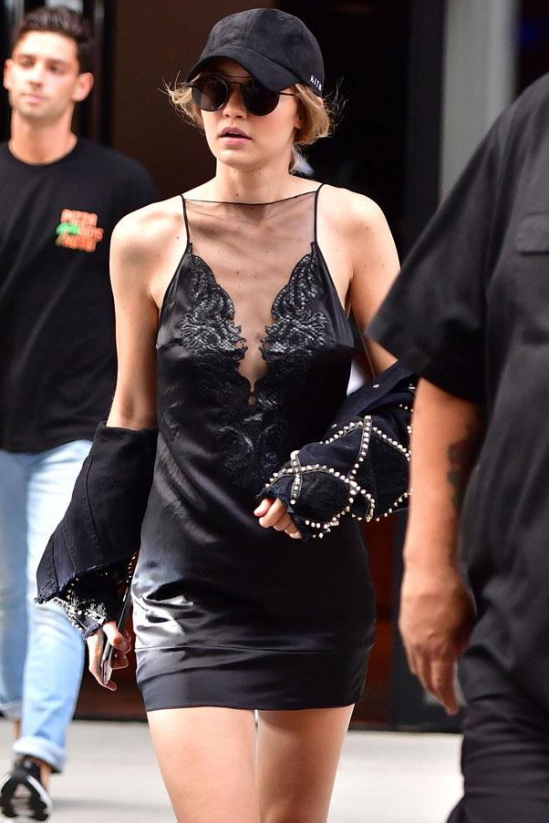 Hadid wears a silk slip dress, embellished jacket worn off the shoulder, black cap and aviators in NYC.