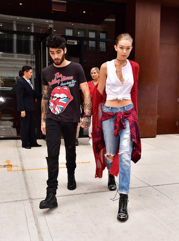 Gigi looked casual as she made her way through New York with Zayn, wearing a cosy, fuzzy red cardigan, distressed denim, a white knotted crop top and a plaid flannel tied around her waist. This grunge look would be nothing if not finished with some black combat boots.