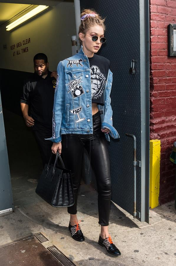 The model donned a rolling stones tee, Unravel lace-up leather leggings, Frame denim jacket with patches, patent leather oxfords, a crocodile leather handbag and rounded sunglasses when she left the Marc Jacobs show at New York fashion week.