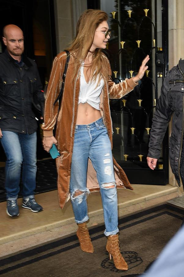 Gigi stepped out in Paris wearing a camel velvet coat, matching lace-up suede boots, a white tee (knotted, of course) and distressed boyfriend jeans.