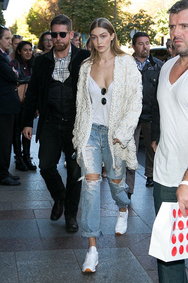 Hadid left the Paris Miu Miu show coordinating a pearl braided Jonathan Simkhai jacket with pearl-embellished ripped boyfriend jeans, a low cut white tee, round sunglasses and white Reebok trainers.