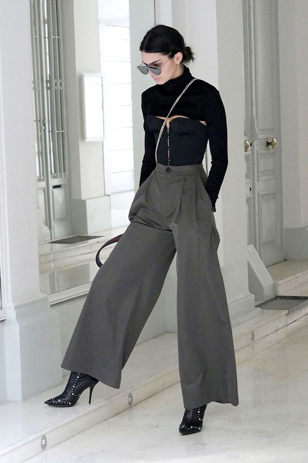 Stepping out in Paris, Kendall donned a super-cropped black turtle neck that barely touched the top of her black corset top. She paired these with wide leg olive green trousers and black ankle boots.<br><br> Image: Splash