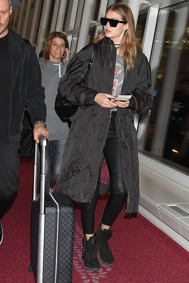 Arriving in Tokyo, Hadid wore a Tommy x Gigi graphic sweater, quilted leather leggings, a dark trench coat and booties. She accessorised with a studded wrap choker, futuristic sunglasses and her checkered luggage and leather backpack.