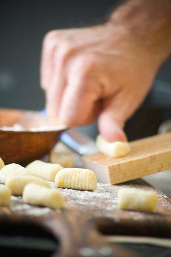 """<strong>GNOCCHI</strong> <br><br> NYAWK-kee <br> <em>Italian thick, soft dough dumplings, first course alternative to soup. </em><br> Eat24, an online food delivery service, puts gnocchi in their top ten list of mispronounced food words. The problem is that Italian <em>gn </em>which has an <em>ny </em>sound. It shouldn't be that hard for us English speakers to say, however. After all, the Italian gn is already familiar- most of us say lasagna correctly. <br> Thr problem with gnocchi, though, is that gn is at the beginning, and in English an initial <em>g </em>is usually silent (as in gnome); the <em>n </em>is sounded like normal English. (Except for <em>gnu</em>, which can be pronounced """"nyu"""" but usually isn't.) <br> Gnocchi, as you make have guessed, is plural. In the extremely unlikely event you want only one of these small foods, ask for gnoccho; that's the singular. But that would be like asking for a strand of spaghetti. You'll probably get stares even if you do pronounce the singular correctly."""