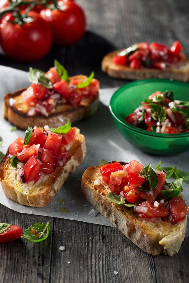 """<strong>BRUSCHETTA</strong> <br><br> broo-SKEH-tah <br> <em>Italian specialty antipasto- grilled bread with olive oil, garlic, tomatoes, salt and pepper, sometimes also with cheese or other toppings. </em><br> Here's a food we've loved for years that we've always pronounced """"broo-SHET-ta""""- and no one ever corrected us. Probably the waiters were too polite (or they didn't know either). In a survey of the most commonly mispronounced food words done by the Chicago Tribune, bruschetta easily made it into the top ten. <br> For the record, it's pronounced """"broo-SKEH-tah""""- with a hard <em>ch </em>sound, as in modern Italian. The word comes from the old Tuscan dialect and is derived from the word <em>bruscare </em>meaning """"to roast over coals."""" And that word probably comes from the late Latin word <em>brusicare</em>, to burn, which suggests that this delicious dish was probably eaten as far back as in the days of Julius Caesar. Then it was a humble farmers' dish: a hunk of moistened stale bread toasted over a fire, then rubbed with olive oil and garlic (but no tomatoes- they didn't make it to Europe until the 1500s). <br> Quick tip for food snobs: if you want to sound truly knowledgeable and annoying, when ordering more than one bruschetta, use the correct plural: not <em>bruschettas</em>, but <em>bruschette</em>."""