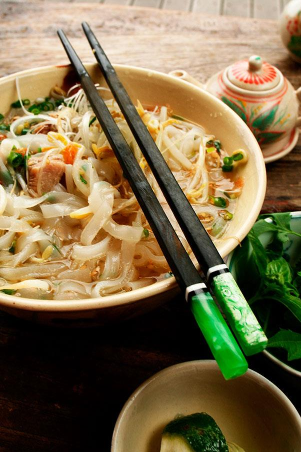 """<strong>PHO </strong><br><br> fuh <br> <em>Vietnamese noodles, served in a beef (and sometimes chicken) broth. </em><br> Here's a well known foodie joke to remind you how to pronounce these wonderful Vietnamese noodles: Q: What do you call a line in a Vietnamese noodle shop? A: Phô Queue. <br> Groan. But yes, it's pronounced """"fuh""""- a slightly rolling uh sound, as in fur without the r, or almost exactly like the French word for fire, <em>feu</em>. And sure enough, many linguists trace the beginnings of pho back to Hanoi of the 1860s under French rule, and perhaps to pot-au-feu (pot on the fire)- the name for a classic Burgundian beef stew made with vegetables. <br> Before then, the Vietnamese rarely ate beef, but with the French, it became a major food item (although phô can be also made with chicken, called phô ga). The Vietnamese added noodles to the """"pot"""" and then chopped off the """"pot-au"""" from the classic French dish's name, and thus a new all-Vietnamese classic was created. But others (particularly in China) trace phô's origins to the beef-eating Chinese, with a Chinese word for noodles, <em>fen</em>, transmogrifying into <em>fuh </em>in Vietnamese. Whatever the origins, at least everyone agrees on one thing: it's not pronounce fo."""