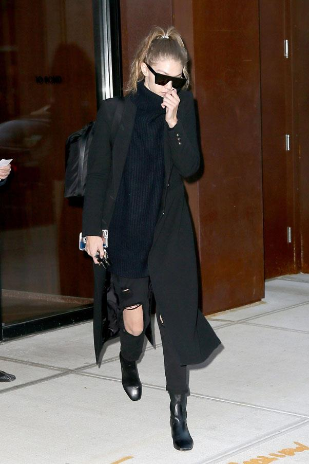 Gigi matched a black turtleneck and distressed 7 For All Mankind jeans, with a black Smythe coat and Sandro ankle boots on her way to JFK airport.