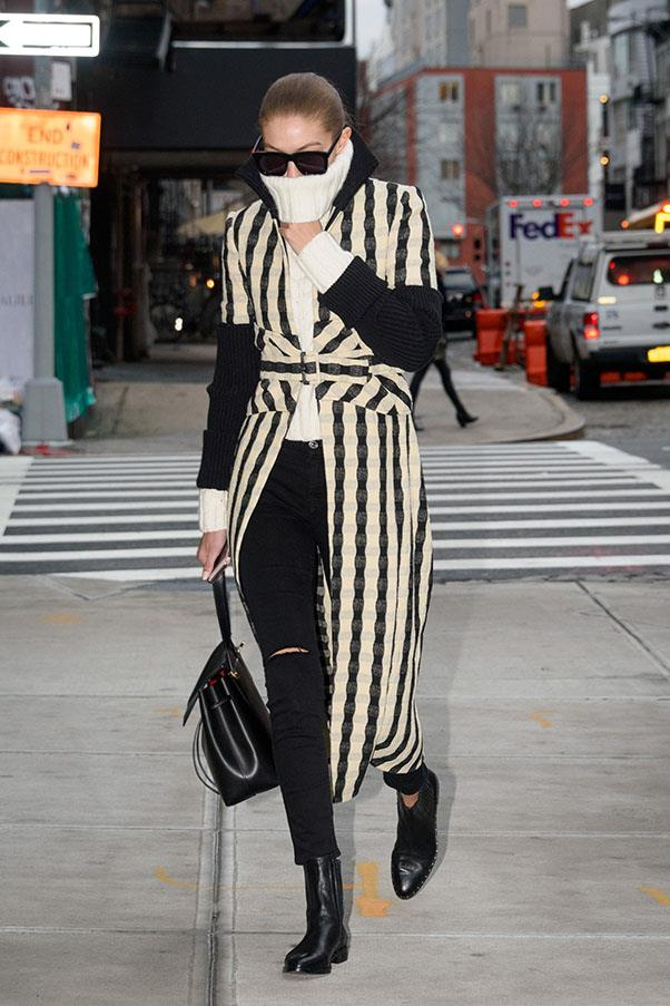 Gigi rugs up in a turtle neck, coat and black jeans on the streets of Manhattan.