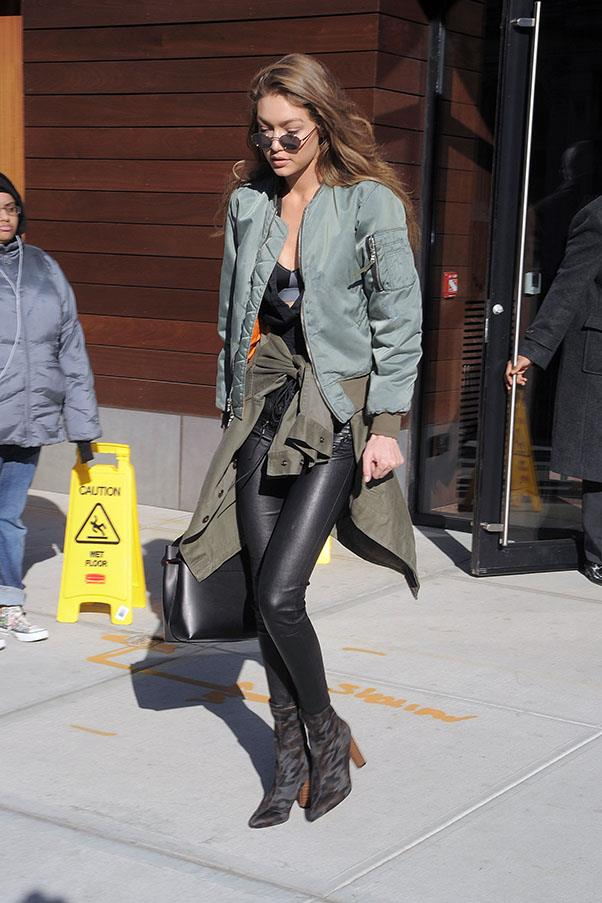 Gigi teams her all black outfit up with a khaki bomber and camo-print boots.
