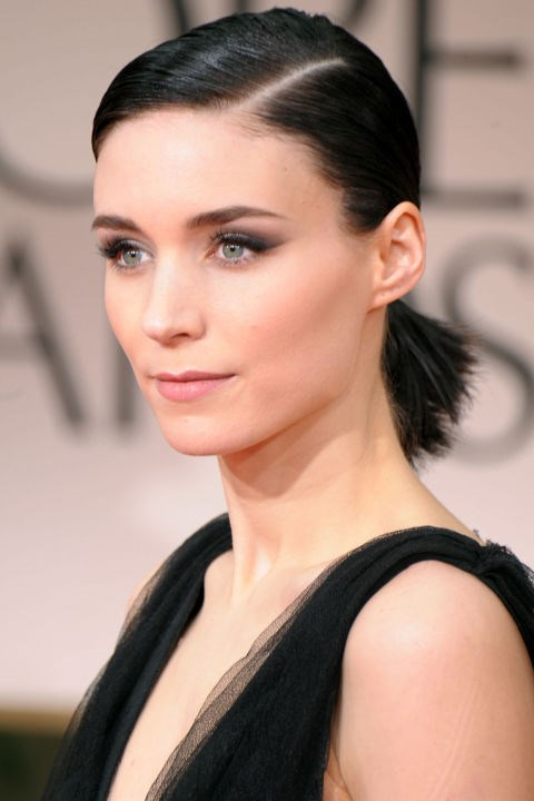 <strong>ROONEY MARA</strong> <br><br> Actress Rooney Mara burst onto the scene in 2011's *Girl With The Dragon Tattoo*. But it was her press tour looks—full of graphic shapes, punk influences, and edgy sex appeal—that solidified Mara as a force in beauty and fashion. Here, she slicked her jet-black hair into a sculptural ponytail while taking a softer approach with a bit of black eyeshadow.