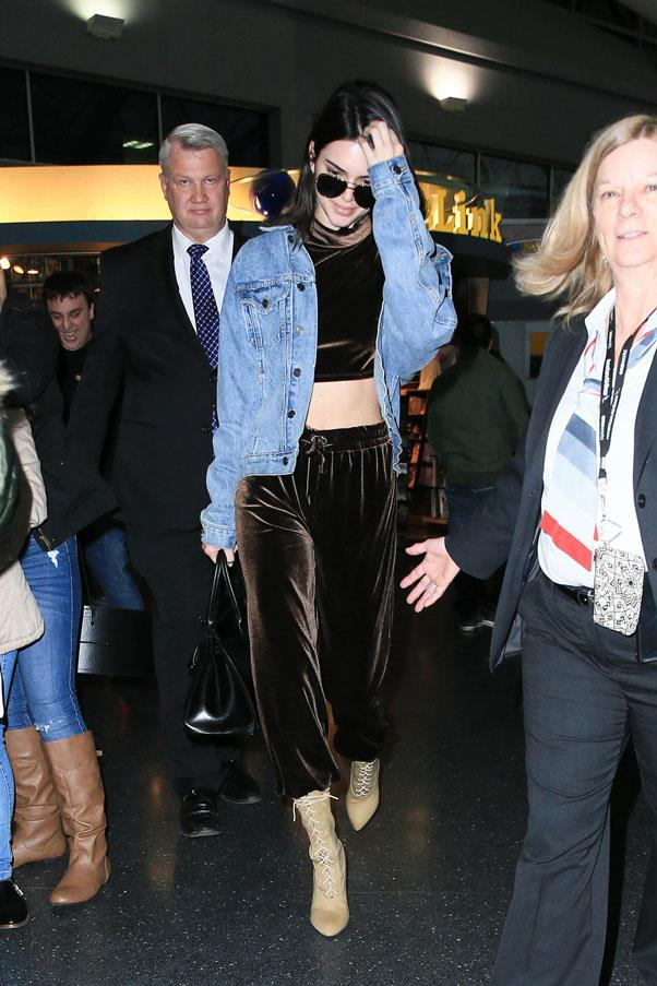 Kendall took airplane comfort to a stylish new level, wearing velvet sweatpants and a top to match, a denim jacket and nude lace up booties, paired with aviator sunglasses.