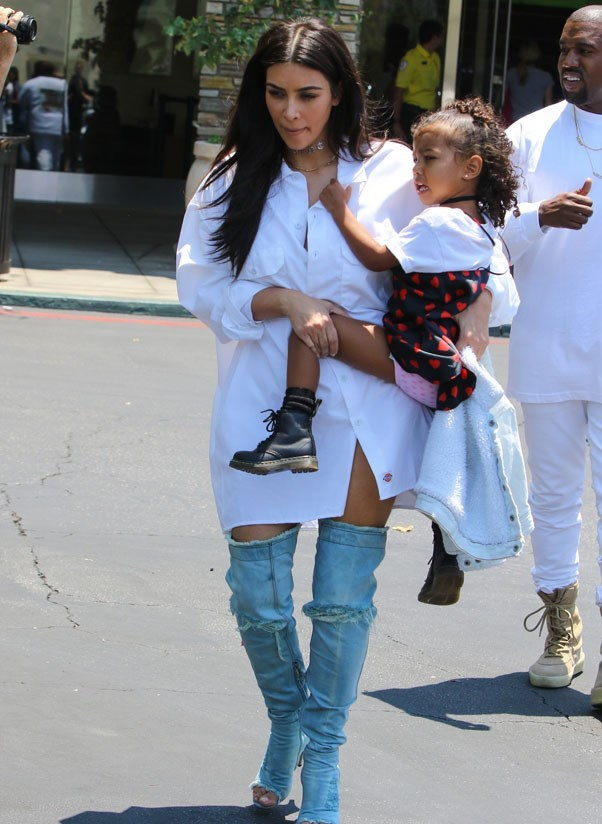 <strong>July 25th, 2016</strong><br><br> Kim wore an oversized white shirt with ripped over-the-knee open-toe denim boots while out with daughter North in Los Angeles.