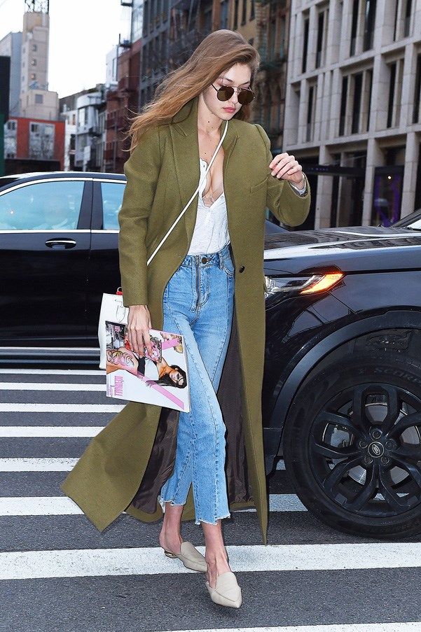 Wearing a forest green coat paired with blue jeans and slides.