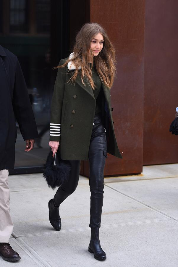 In a dark green coat with black pants and boots.