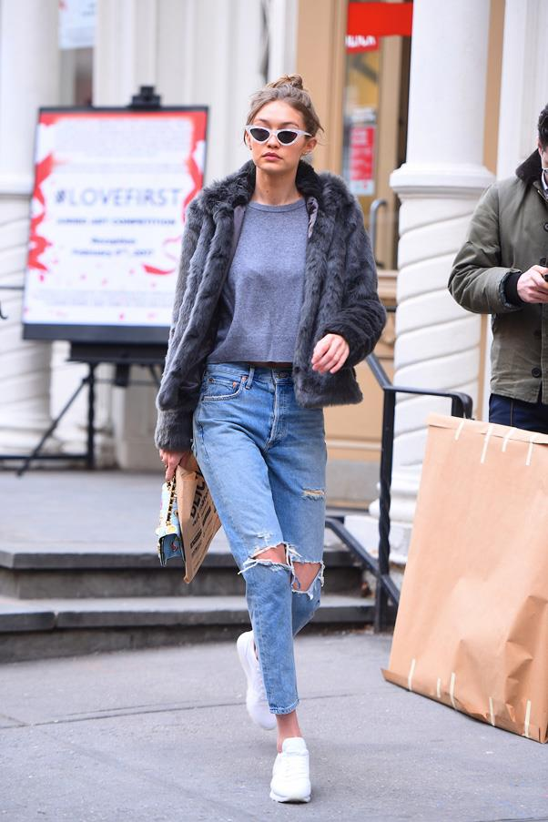 In white sneakers, jeans, a grey tee underneath a fluffy jacket and cat-eye sunglasses.