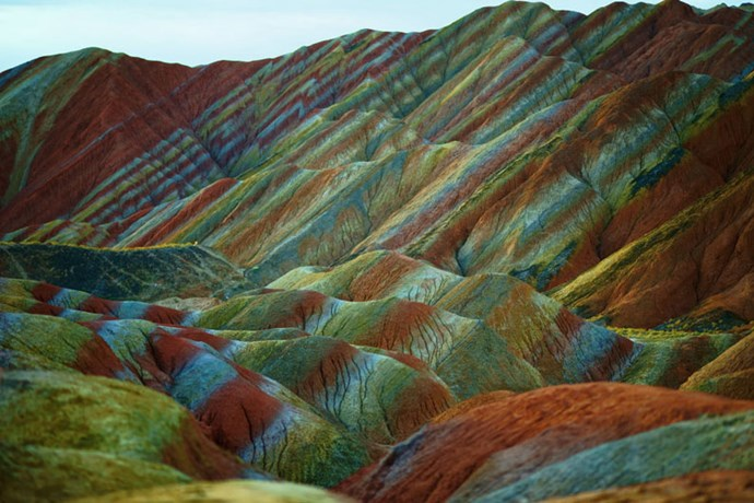 """<strong>1. Danxia Landform: Zhangye, China</strong> <br><br> Danxia landscapes are steep cliffs of red rock and they can be found in six areas around the country. <a href=""""http://whc.unesco.org/en/list/1335"""">Zhangye Danxia</a> is known as the nation's most beautiful, though, with its uniquely shaped, multicoloured rock face."""