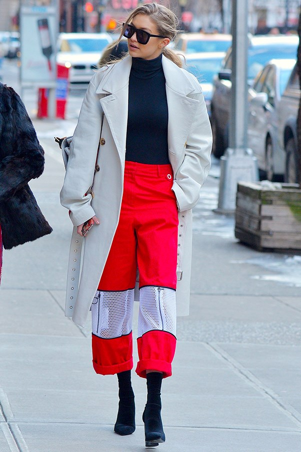 Gigi braves the New York winter in a long, white coat, a black turtleneck and bright red, baggy pants.